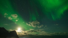 Arctic chill: pro surfer rides waves under the Northern Lights