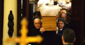 The remains of poet John Montague are carried by his nephews Andrew and Turlough Montague with poet Theo Dorgan (left) at his  funeral mass. Photograph: Alan Betson