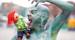 Bosco meets Erik Sprague aka The Lizardman in Dublin's Smithfield for the 2016 Laya City Spectacular. This year's event takes place from July 7th-9th (Dublin), 15th-16th (Cork). Photograph: Leon Farrell/Photocall Ireland