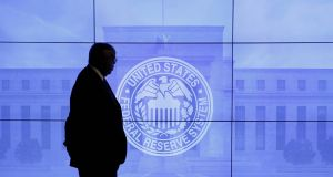 A security guard is silhouetted at an image of the Federal Reserve in Washington DC. Stocks in New York edged lower ahead of the Fed's announcement, as new data pointed to a loss of momentum in economic growth in the fourth quarter. Photograph: Kevin Lamarque/Reuters