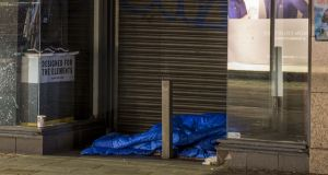 A homeless person sleeps in front of a shop on Grafton Street in Dublin city centre.  Photograph: Dara Mac Donaill / The Irish Times
