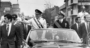 General Augusto Pinochet (left), head of the Chilean military junta, waves from the motorcade 11 September 1973 in Santiago, shortly after his coup d'etat that killed socialist President Salvador Allende. Photograph:  STR/AFP/Getty Images