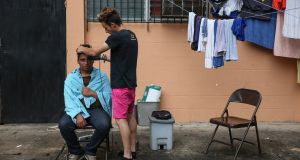 A Cuban man gives another a haircut outside a Caritas centre housing migrants in Panama City. Photograph: Sally Hayden