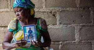 Toussaint's grandmother Pauline Yassedi with a portrait of the boy. She was at home when she heard the accident taking place. Photograph: Andrew Esiebo/The New York Times