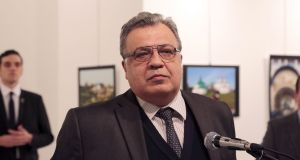 The Russian ambassador to Turkey Andrey Karlov speaks at a gallery in Ankara. He was shot dead during his speech. The gunman is seen at rear on the left. Photograph: Burhan Ozbilici/AP Photo