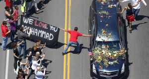 A well-wisher holding a banner touches the hearse carrying the remains of Muhammad Ali during the funeral procession for the three-time heavyweight boxing champion in Louisville, Kentucky in June.  Photograph:  Reuters