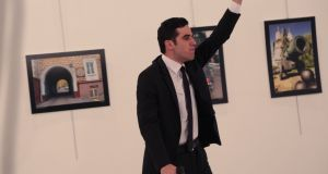 An unnamed gunman gestures after shooting the Russian ambassador to Turkey, Andrei Karlov, at a gallery in Ankara, Turkey. Photograph: Burhan Ozbilici/AP Photo