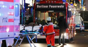 A survivor of  is rescued on a stretcher near a Christmas market in Berlin, Germany. Photograph: Fabrizio Bensch/Reuters