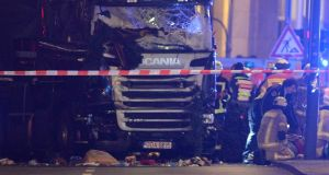 Rescue workers around a truck which  crashed into a Christmas market close to the Kaiser Wilhelm memorial church in Berlin, Germany on Monday evening. At least nine people have died in the incident. Photograph:  Paul Zinken/EPA
