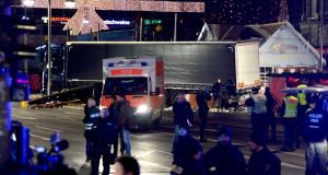 Police and rescue workers  next to a truck  after it crashed into a Christmas market, close to the Kaiser Wilhelm memorial church in Berlin, Germany, killing at least nine people. Photograph: Maurizio Gambarini/EPA