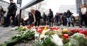 People gather to lay down flowers outside the Gedaechniskirche near the area where a truck which ploughed into a Christmas market. Photograph: Pawel Kopczynski/Reuters
