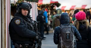 Heavily armed police stand guard  at the Columbus Circle Holiday Market in New York City as part of increased security  measures throughout the city. Photograph: Drew Angerer/Getty Images