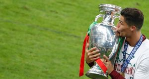 Euro 2016  final: Portugal's Cristiano Ronaldo kisses the trophy on the pitch. Photograph: Reuters/Christian Hartmann
