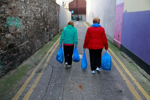Each person queuing at the Capuchin Centre has a ticket entitling them to two blue plastic bags of food – one of non-perishables including tea, sugar, cereals, tinned fish, tinned beans, custard, chocolates and biscuits, and one of such perishables as milk, cheese, a chicken and butter. Photograph: Nick Bradshaw
