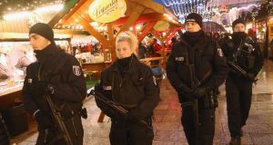 Heavily-armed police walk through the reopened Breitscheidplatz Christmas market on Thursday. Photograph:  Sean Gallup/Getty Images