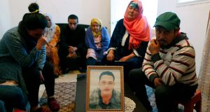 The family of Anis Amri sits around a portrait of him in their home in Oueslatia, Tunisia, on Thursday. Photograph: Mohamed Messara/EPA