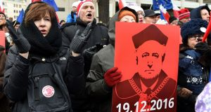 Protesters with a picture of Andrzej Rzeplinski, the outgoing head of Poland's constitutional court, at an anti-government rally in front of the court  in Warsaw. Photograph: Janek Skarzynski/AFP/Getty Images