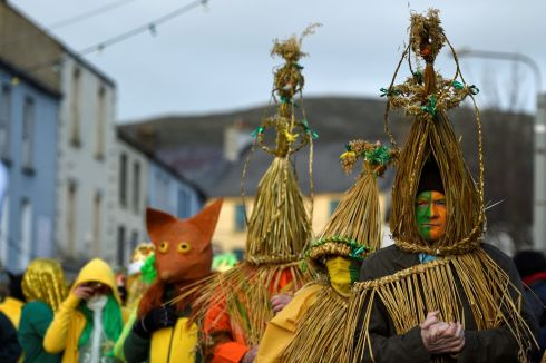 The bird is then paraded from house to house by masked wrenboys dressed in straw suits and colourful clothing.  Photograph: Clodagh Kilcoyne/Reuters