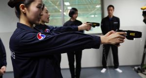 Flight attendants of Korean Air Lines Co. learn how to use stun guns against in-flight violence during training in Seoul, South Korea, on Tuesday. The flag carrier has instructed its flight crew to resort to active force when needed after unruly behavior by a  passenger last week became a widely publicised controversy. Photograph: Yonhap/EPA