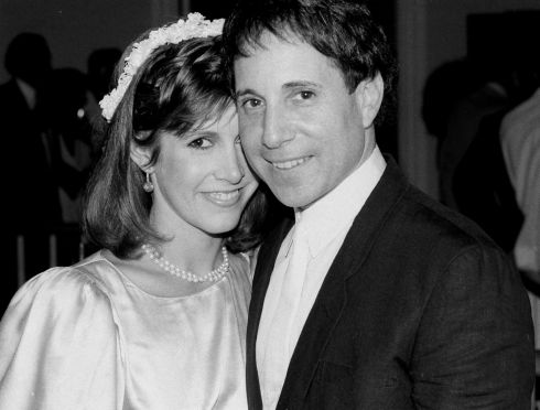 August 1983:  Carrie Fisher and singer Paul Simon stand together at their apartment in New York during their wedding reception.  Photograph: Mario Suriani