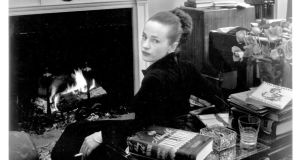Maeve Brennan sitting at the fireplace. Photograph from Angela Bourke's Maeve Brennan: Homesick at The New Yorker