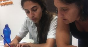 Sabina Bustos and Nadia Bolgan, of the property records office in Laboulaye, Argentina, looking at documents