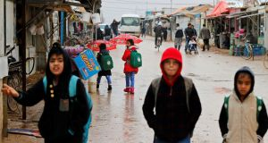 Syrian refugee children walk to  school during rainy weather at  Al Zaatari refugee camp in  Jordanian city of Mafraq, near  border with Syria. Photograph:  Muhammad Hamed/Reuters