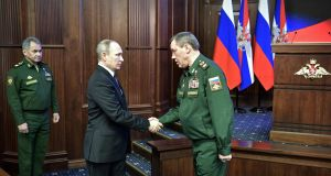 Vladimir Putin (C) shakes hands with Russia's head of the armed forces general staff, Valery Gerasimov (R). Photograph: Alexey Nikols/Getty Images