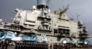 A  photo dated January 2012 shows a crew lined up aboard Russian aircraft carrier Kuznetsov in the sea port city of Tartous, Syria. Photograph: EPA/Sana