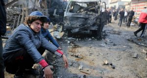 People at the scene of  a car bomb explosion at a crowded outdoor market in Baghdad on Sunday. Photograph: Karim Kadim/AP