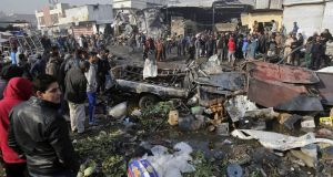 People inspect the scene after a car bomb explosion at a crowded outdoor market in Baghdad on Sunday. Photograph:  Karim Kadim/AP
