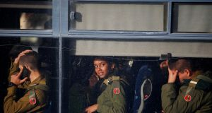 Israeli soldiers sit in a bus as they leave the scene. Photograph: Ronen Zvulun/Reuters