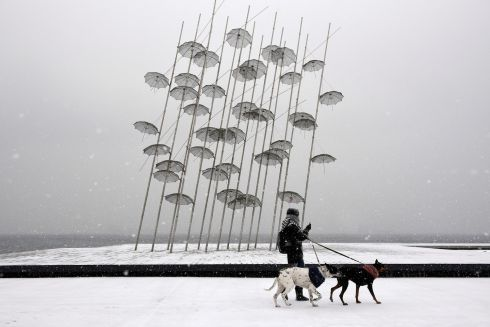 "THESSALONIKI: A woman with two dogs walks past the ""Umbrellas"", the sculpture by Giorgos Zogolopoulos during heavy snowfall at the seaside promenade of the northern port city of Thessaloniki, Greece. Photograph: Alexandros Avramidis/Reuters"