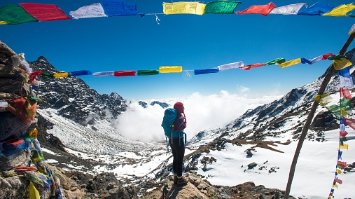 A woman stands among prayer flags marking the top of the Laurebina La which is the pass between the Langtang region and Helmabu in Nepal