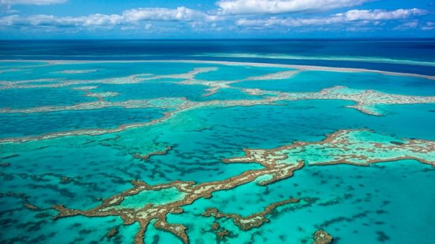 Aerial photo of Great barrier reef showing reef area with some blue water and slightly cloudy sky in background.