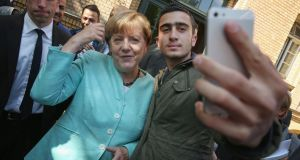 Anas Modamani and Angela Merkel at Berlin's AWO Refugium Askanierring shelter for migrants on September 10th, 2015. Photograph: Sean Gallup/Getty Images