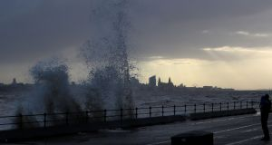 Waves crash over the promenade at New Brighton in Wirral, UK. Photograph: Peter Byrne/PA Wire