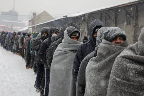 BELGRADE: Migrants wait in line to receive a plate of free food as snow falls outside a derelict customs warehouse in Belgrade, Serbia. Photograph: Marko Djurica/Reuters