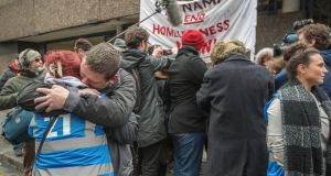 Volunteers hug each other as homeless residents leave Apollo House on Thursday. Photograph: Brenda Fitzsimons