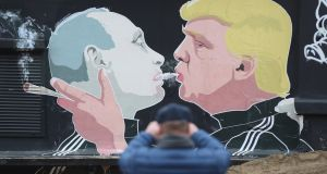 A  man photographs a mural showing Donald Trump blowing marijuana smoke into the mouth of Vladimir Putin in Vilnius, Lithuania. Photograph: Sean Gallup/Getty