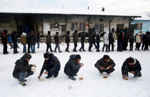 BELGRADE, SERBIA: Five migrants squat in the snow as they eat a warm meal distributed by aid groups as others queue for their portion outside a crumbling warehouse serving as a makeshift shelter in Belgrade, Serbia. Migrants have been exposed to freezing temperatures and snow as extreme winter weather gripped Serbia and other parts of Europe. Photograph: Darko Vojinovic/AP Photo