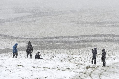 PEAK DISTRICT, DERBYSHIRE: A family takes a picture amid snow on Mam Tor hill in the Peak District, Derbyshire, England, as blizzard conditions begin to sweep in. Photograph: Joe Giddens/PA Wire
