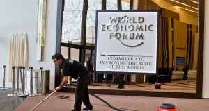 A man cleans a carpet ahead of the World Economic Forum in Davos, Switzerland. Photograph: Michel Euler/AP