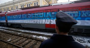 "A railway worker stands by the  train bearing the words ""Kosovo is Serbia"" in 20 languages leaving Belgrade for Kosovo. Photograph: Darko Vojinovic/AP"