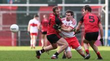 Down's Barra O'Hagan with Benny Heron of Derry compete for a loose ball on Sunday. Photograph: Matt Mackey/Inpho