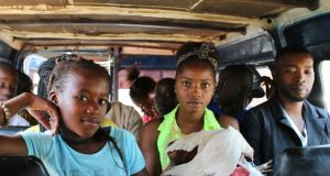 TV salesman Kaba Fall (far right) and two young Gambian women on a minibus bound for Senegal amid tensions over the transition to a new presidency. Photograph: Lorraine Mallinder