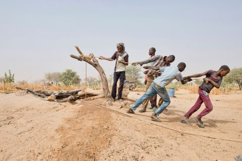 Men pull a rope to raise water from well near the town of Zinder in Niger. The country, one of the world's poorest, faces increasing demands upon its scarce water resources as its population grows.