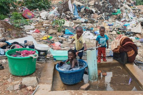 Children bathe at a water pump in the township of Alexandra in Johannesburg, South Africa. Migrants from surrunding countries, forced from their homes by poverty and drought, move to wealthier South Africa in search of a better life but often find that the life they left behind was no worse.