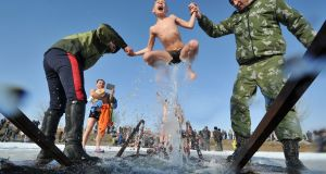 COLD CALL: Cossacks help a boy to take a bath in the icy waters of a lake during the celebration of the Epiphany holiday near the village of Leninskoe, some 15 km of Bishkek. Photograph: Getty Images