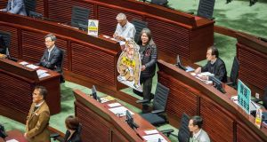 "Leung Kwok-hung, known as ""Long Hair"", brings a cut-out of a monkey bearing the likeness of Hong Kong's chief executive CY Leung  into the chamber before Mr Leung's final policy address to the legislative council on Wednesday. Photograph: Isaac Lawrence/AFP/Getty Images"
